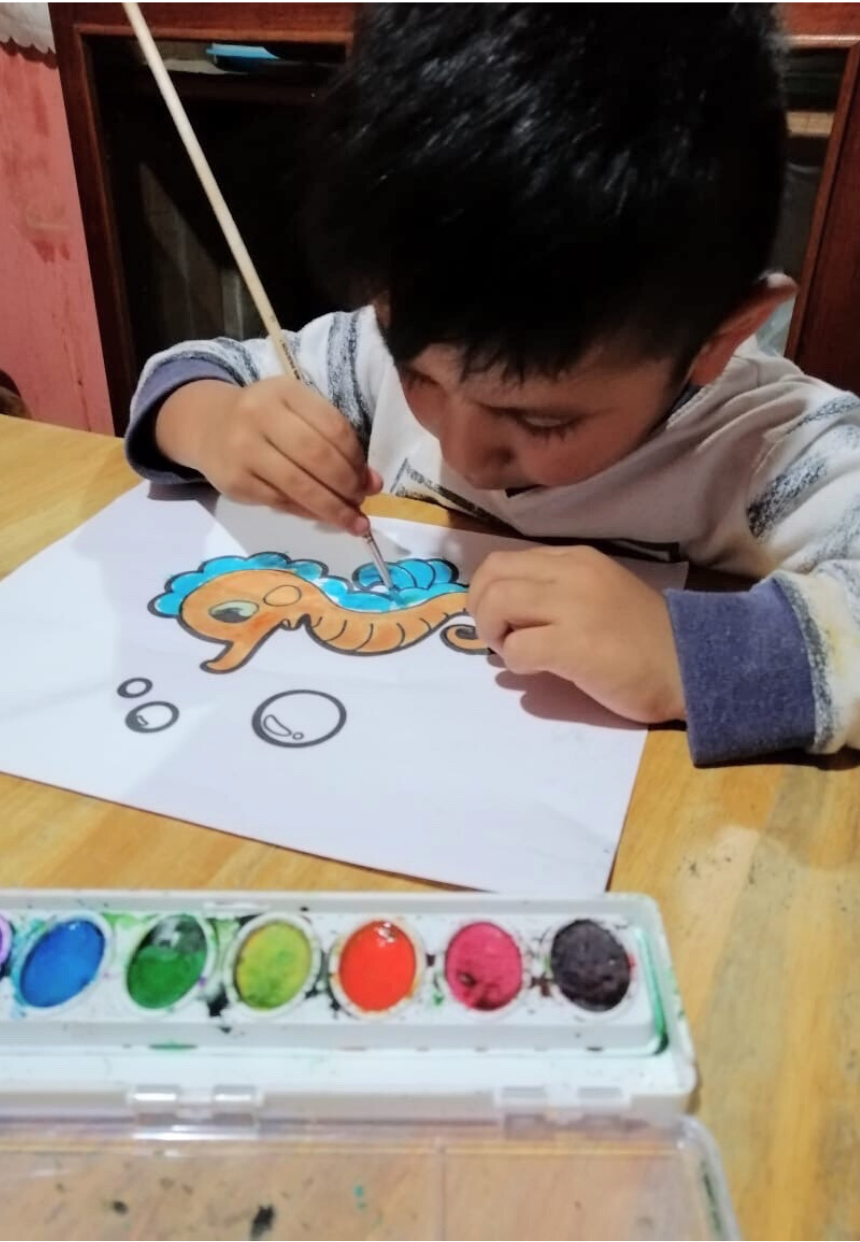 Maya Childcare student painting a picture at home